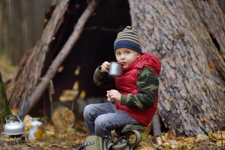 Little boy scout during hike in forest on autumn day. Child is cooking tea with help tourist gas burner and eating sandwich. Concepts of adventure, scouting and hiking tourism for kids.