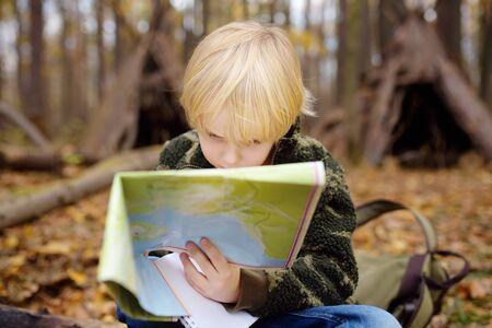 Il ragazzino scout sta facendo orienteering nella foresta. Il bambino è seduto su un albero caduto e sta guardando sulla mappa sullo sfondo della capanna del tepee. Concetti di avventura, scoutismo e turismo escursionistico per bambini.