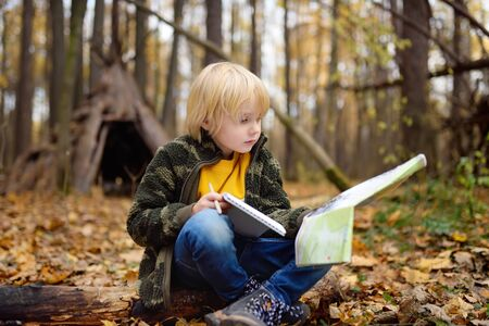 Little boy scout is orienteering in forest. Child is sitting on fallen tree and looking on map on background of teepee hut. Concepts of adventure, scouting and hiking tourism for kids. Stock Photo