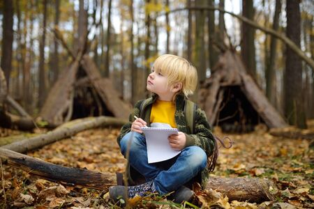 Little boy scout is orienteering in forest. Child is sitting on fallen tree and looking on map on background of teepee hut. Concepts of adventure, scouting and hiking tourism for kids.