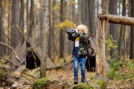Little boy scout with binoculars during hiking in autumn forest. Child is looking through a binoculars. Behind the child is teepee hut. Concepts of adventure, scouting and hiking tourism for kids. Archivio Fotografico