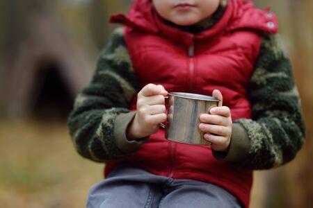 Little boy scout durante le escursioni nella foresta autunnale. Il bambino sta riposando e bevendo tè caldo. Concetti di avventura, scoutismo e turismo escursionistico per bambini. Archivio Fotografico