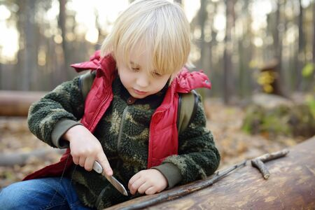 Little boy scout is playing with knife in the forest. Child cuts with a knife on a log. Concepts of adventure, scouting and hiking tourism for kids.