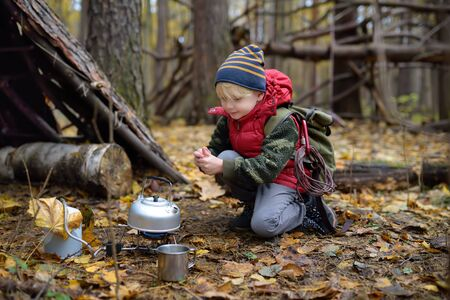 Little boy scout during hike in forest on autumn day. Child is cooking tea with help tourist gas burner. Behind the child is teepee hut. Concepts of adventure, scouting and hiking tourism for kids.