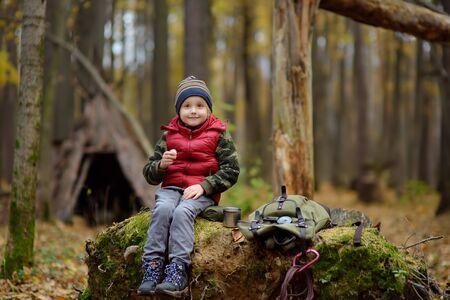 Little boy scout during hike in forest on autumn day. Child is drinking hot tea and eating sandvich. Behind the child is teepee hut. Concepts of adventure, scouting and hiking tourism for kids.