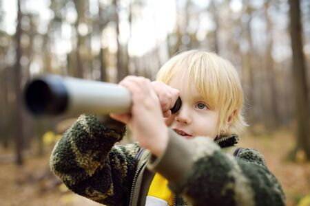 Little boy scout with spyglass during hiking in autumn forest. Child is looking through a spyglass. Concepts of adventure, scouting and hiking tourism for kids.