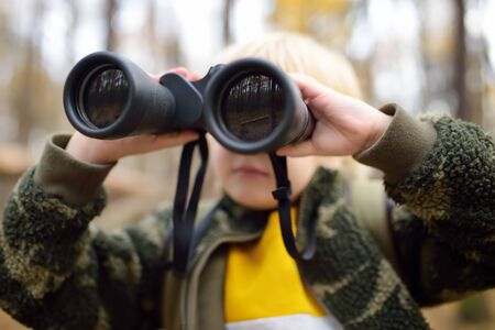 Little boy scout with binoculars during hiking in autumn forest. Child is looking through a binoculars. Concepts of adventure, scouting and hiking tourism for kids. Archivio Fotografico