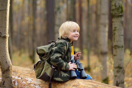 Little boy scout con il binocolo durante le escursioni nella foresta autunnale. Il bambino è seduto su un grande albero caduto e guarda attraverso un binocolo. Concetti di avventura, scoutismo e turismo escursionistico per bambini.