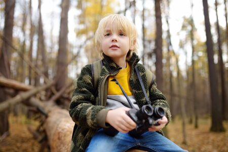 Little boy scout with binoculars during hiking in autumn forest. Child is sitting on large fallen tree and looking through a binoculars. Concepts of adventure, scouting and hiking tourism for kids.