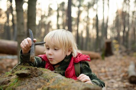 Little boy play with stick in forest on autumn day. Hiking for family with kids. Archivio Fotografico