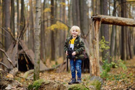 Little boy scout con il binocolo durante le escursioni nella foresta autunnale. Il bambino sta guardando attraverso un binocolo. Concetti di avventura, scoutismo e turismo escursionistico per bambini.