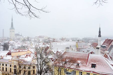 Aerial cityscape view of Tallinn Old Medieval Town on winter day. Snow is covering red rooftops from tiles. St. Olaf's Church spire visible in the distance. Stockfoto