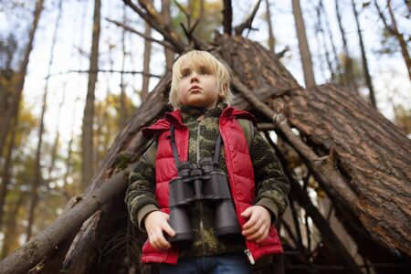 Little boy scout with binoculars during hiking in autumn forest. Behind the child is teepee hut. Concepts of adventure, scouting and hiking tourism for kids.