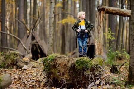 Little boy scout with binoculars during hiking in autumn forest. Child is looking through a binoculars. Concepts of adventure, scouting and hiking tourism.