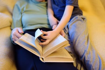 Elderly grandmother and little grandchild reading a book at home. Grandma and grandson. Quality family time.