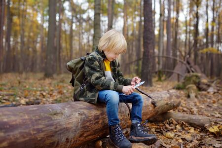 Little boy scout is sharpening a stick with the help knife in the forest. Concepts of adventure, scouting and hiking tourism for kids.