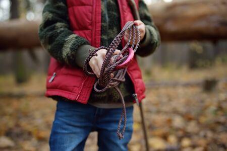 Little boy scout durante le escursioni nella foresta autunnale. Il bambino sta tenendo la corda con la carabina del gancio. Concetti di avventura, scoutismo e turismo escursionistico per bambini.