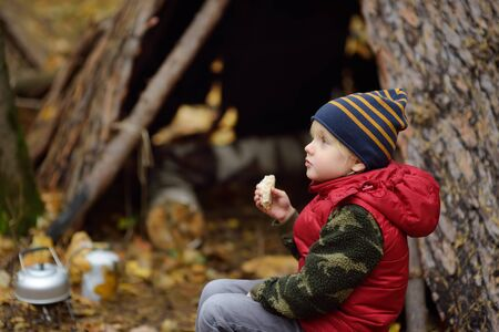 Little boy scout during hike in forest on autumn day. Child is cooking tea with help tourist gas burner and eating sandvich. Concepts of adventure, scouting and hiking tourism for kids.