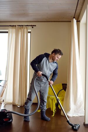 Man vacuuming wooden floor at home. Household chores Foto de archivo - 134487760