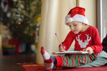 Little boy writing the letter to Santa. Child dreams of a gift that he can receive. Magic mail of Santa Claus.