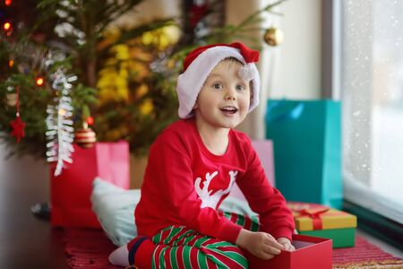 Excited little boy with a Christmas gift under fir tree at home. Portrait of happy kid in Christmas morning. Cozy living room with decorated fir tree