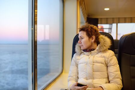 Mature woman is looking on the window at the amazing view of frozen sea during crossing on the ferry boat. Sea travel in winter. 版權商用圖片