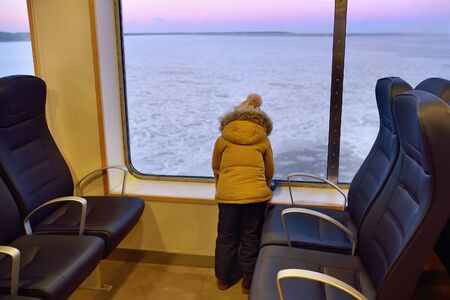 Little inquisitive boy is looking on the window at the amazing view of frozen sea during crossing on the ferry boat. Travel with kids in winter holidays.