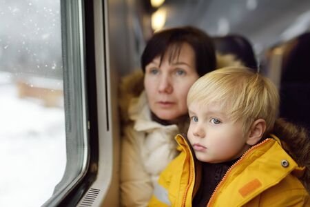 Family looking out of the window of train during travel on cogwheel railwayrack railway in Alps mountains. Winter holidays in SwissGermanItalian Alps