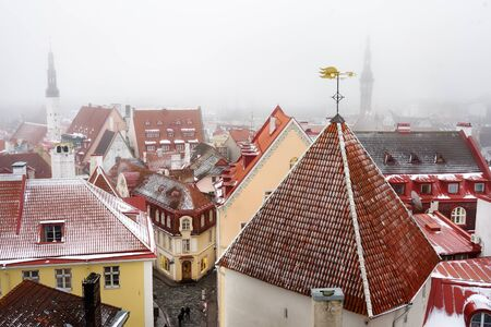 Aerial cityscape view of Tallinn Old Town on winter day. Snow covered red rooftops from tiles, Golden Cockerel weathervane, Town Hall spire, modern office buildings skyscrapers far away.