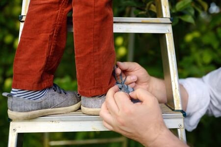 Father tie a lace on the shoe his little son. Child standing on ladder near tree in domestic garden. Safety for little kids. 版權商用圖片