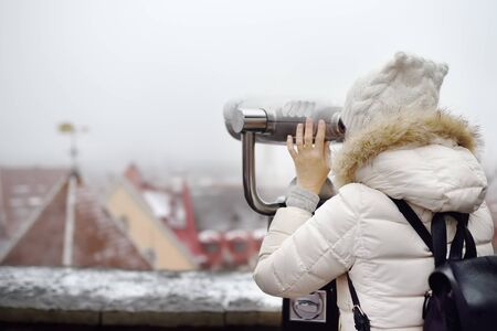 Woman looking through binoculars to the view of Tallinn Old Town on winter day. Snow covered red rooftops from tiles, Golden Cockerel weathervane - romantic view of the snowy roofs of a medieval city. 版權商用圖片