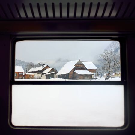 Typical view of small alps village from window of train in snowy winter day. Travel and tourism in winter holidays. 版權商用圖片