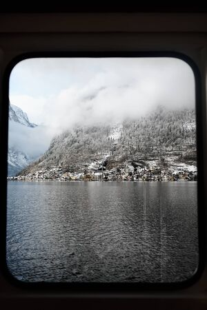 Winter scenic view of village of Hallstatt in the Austrian Alps from window of ship. Famous postcard view of Hallstatt.