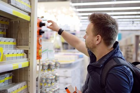 Middle age man checks electric lamps in a hardware store. DIY concept