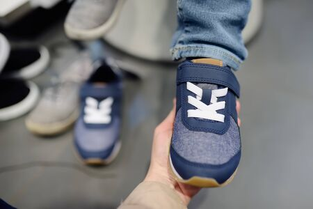 Little boy during shopping with his mother. Kid trying new fashion seasonal sneakers. Child in shopping centermall or baby apparel store.