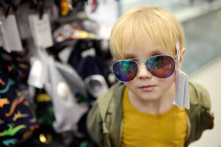 Little boy choosing of sunglasses in store. Child chose fashionable glasses and tries them on. Preparing for summer vacation. Shopping with kids.