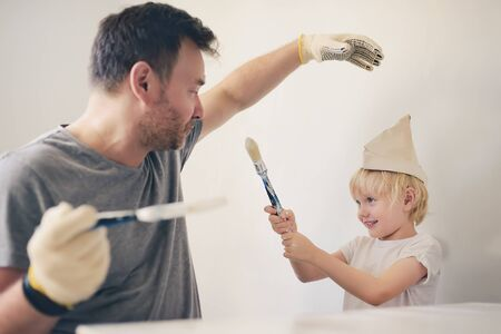 Mature man and little boy having fun with paint brush during repair of room together. Parenthood. Quality family time.