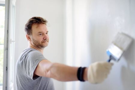 Portrait of a handsome Mature man making repairs in the apartment. The person paints the wall white. Do it yourself. Repair with their hands. 版權商用圖片