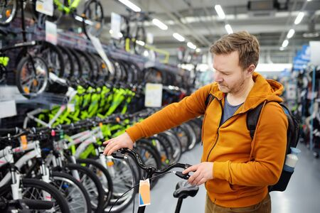 Middle age man choosing bicycle in sport store. Healthy active style of life.