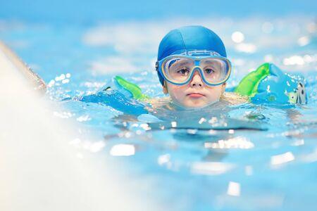 Niño con gafas y brazaletes inflables en piscina. Niño aprendiendo a nadar.