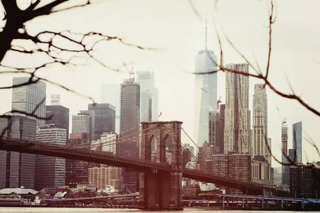 Toned photo of skyscrapers of Manhattan and Brooklyn bridge at winter day. Famous bridge. Postcard view of New York.
