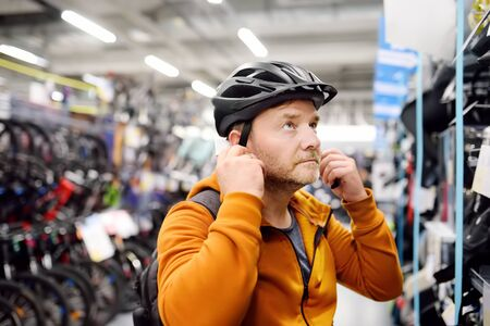 Middle age man choosing and try bicycle helmet in sport store. Healthy active style of life. 版權商用圖片