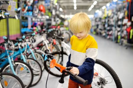 Little boy choosing bicycle in sport store. Healthy active lifestyle for kids.