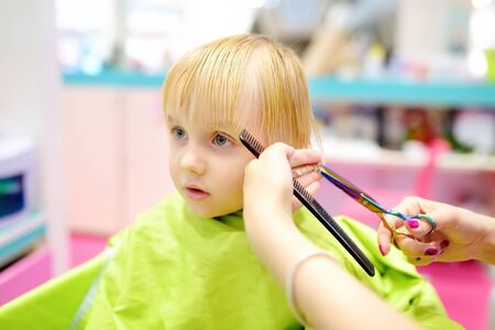Preschooler boy getting haircut. Children hairdresser with professional tools - comb and scissors. Cutting hair for kids. 版權商用圖片