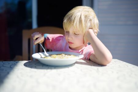 Little boy sitting the table and doesnt want to eat soup. Healthy food. Kids diet. 版權商用圖片