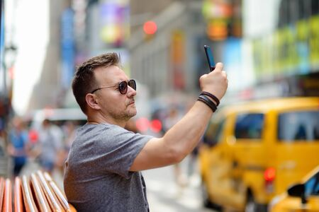 Man tourist shooting or taking selfie on Times Square on sunny summer day, downtown Manhattan. Famous street of New York City. Stock Photo