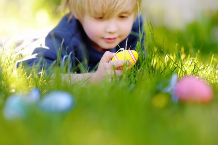 Little boy hunting for egg in spring garden on Easter day. Traditional easter festival outdoors. Focus on multicolor eggs.