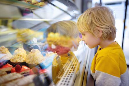 Little boy is admiring cakes and other sweets on the showcase in cafe or supermarket. Diet, unhealthy food, intolerance lactose or gluten in children