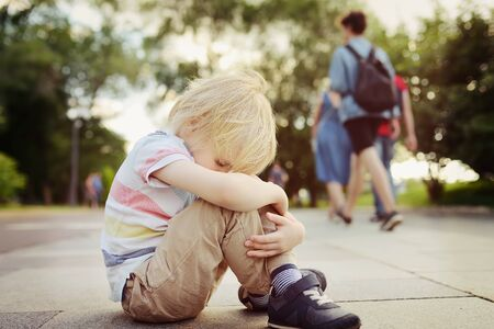 Toned shot of upset little child which was lost in street of city. Run away from home. Quarrel, divorce of parents. Loneliness in a crowd. Stock Photo