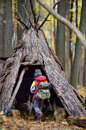 Little boy scout during hiking in autumn forest. Child examining teepee hut in woodland. Concepts of adventure, scouting and hiking tourism for kids. Archivio Fotografico